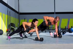 Gym man and woman push-up strength pushup with dumbbell in a crossfit workout